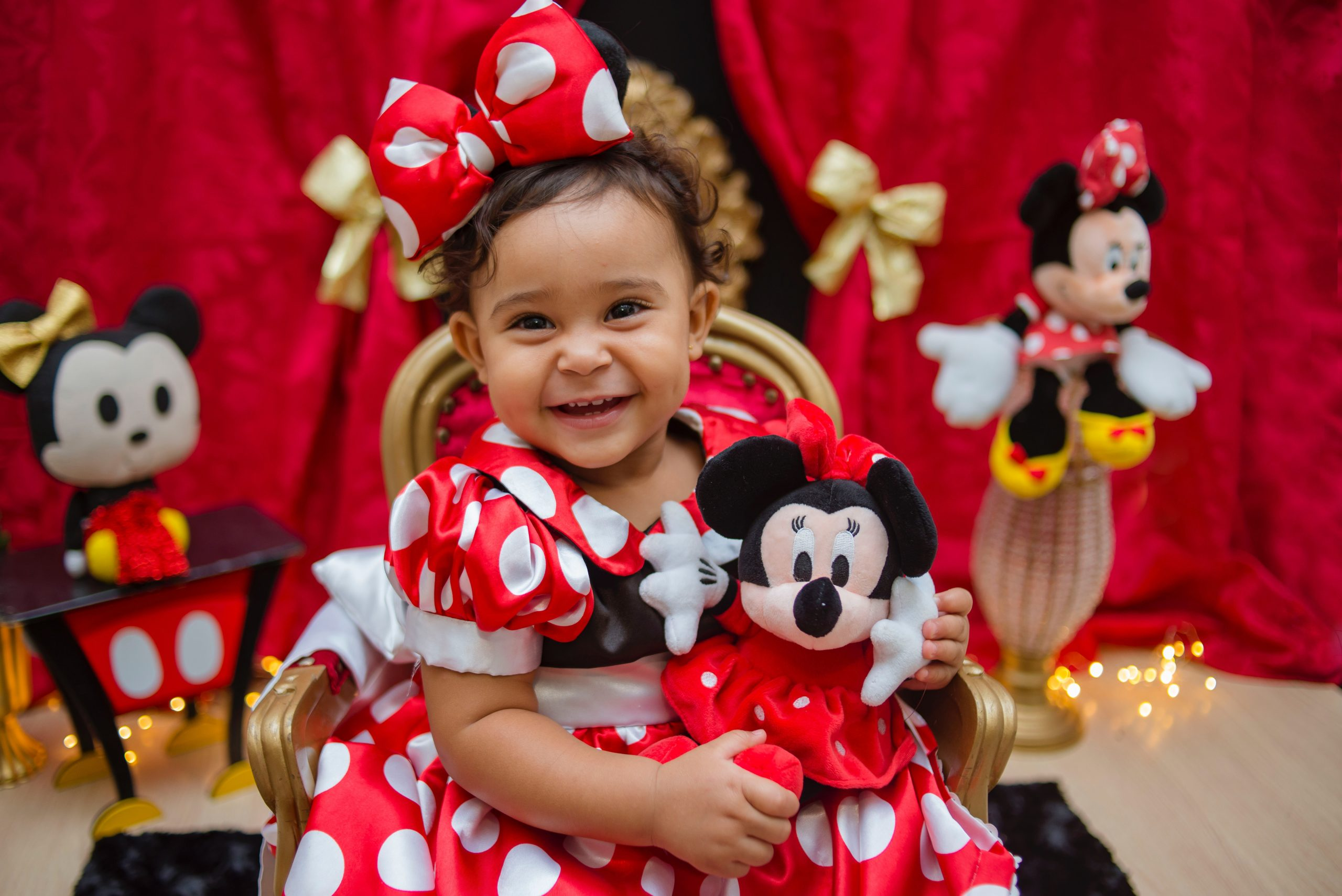 Girl in Red and White Polka Dot Dress Holding Mickey Mouse Plush Toy