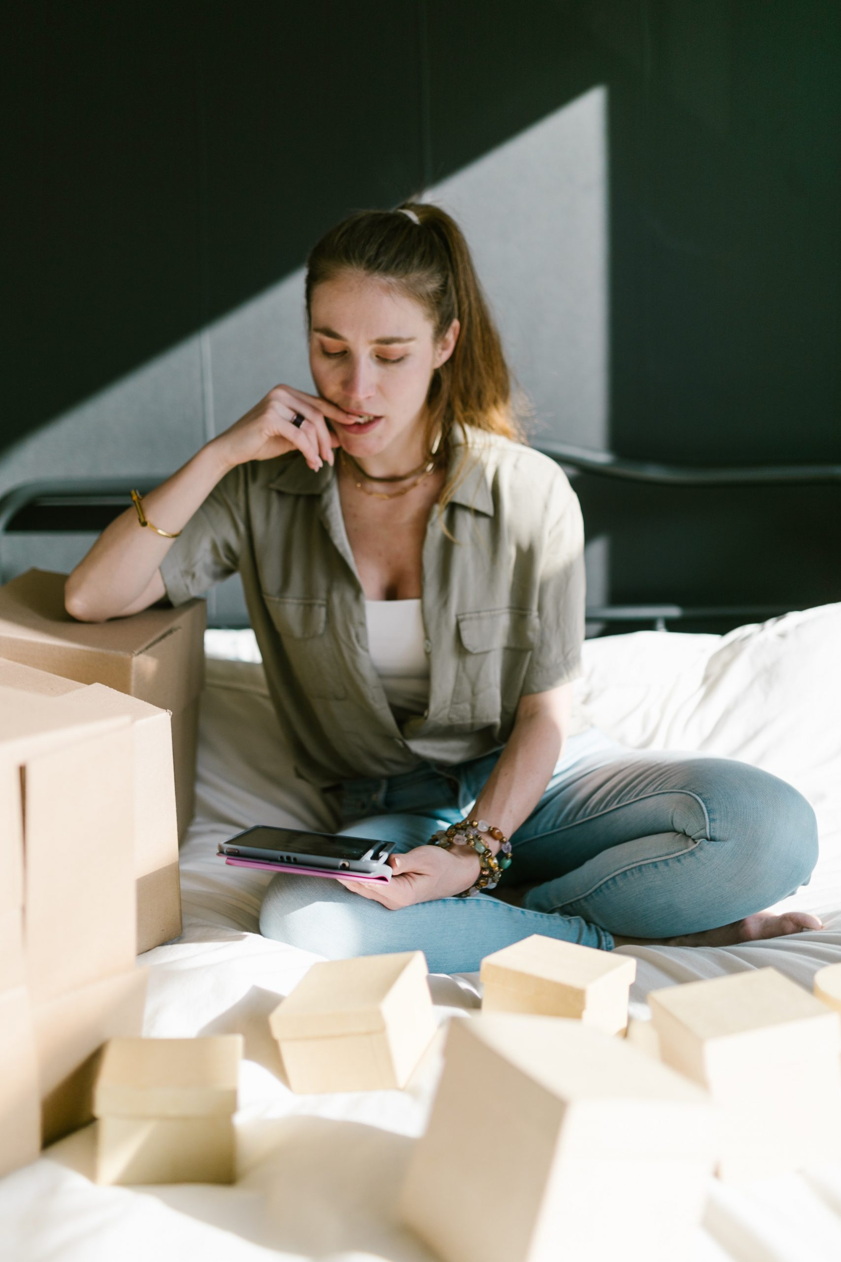 Lady sitting on bed surrounded by small brown boxes