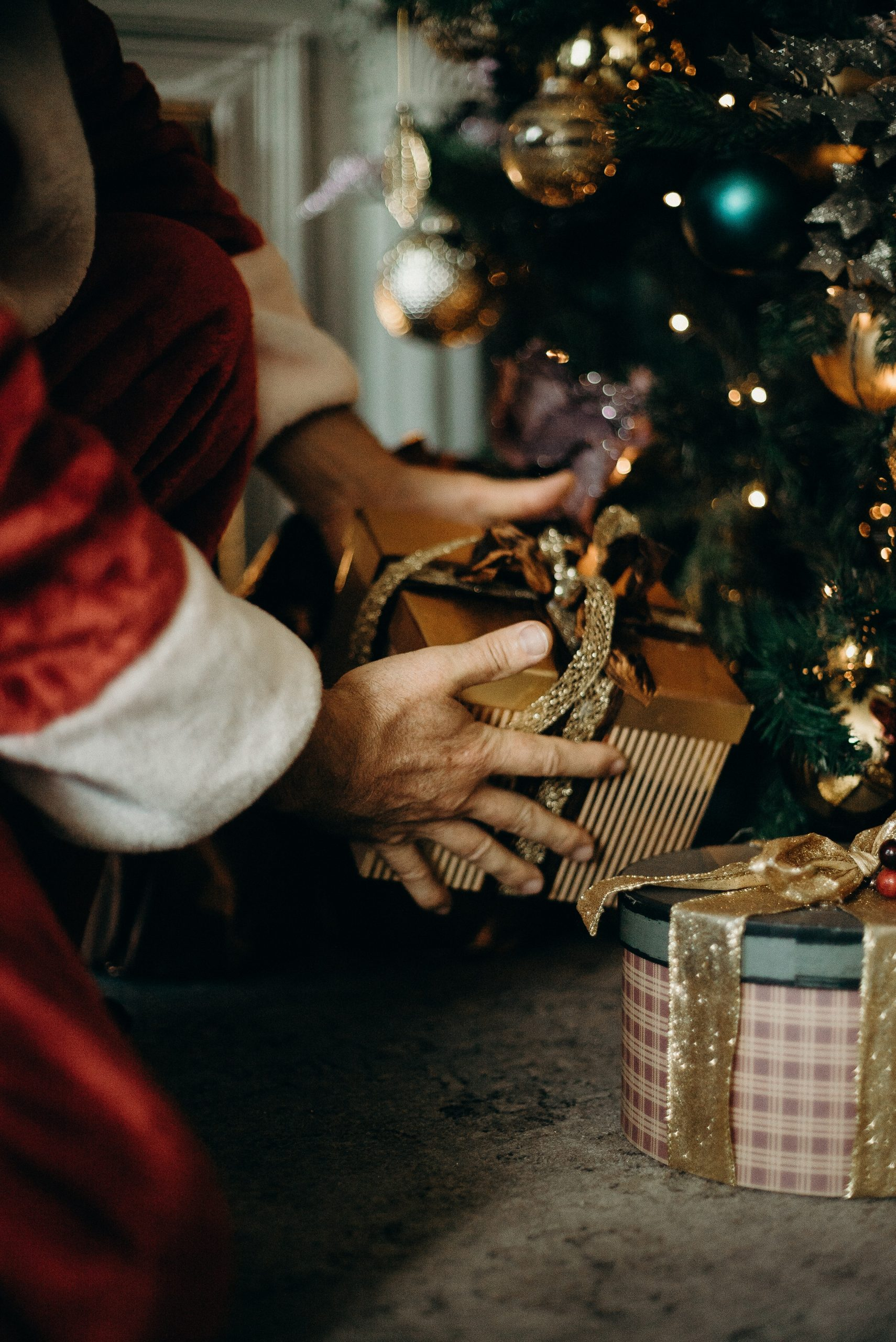 Person Wearing Santa Costume Holding Gold Gift Box